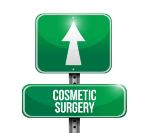 "A green traffic sign with an up arrow and ""COSMETIC SURGERY"" below it"
